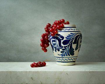 Vase bleu de Delft aux baies rouges