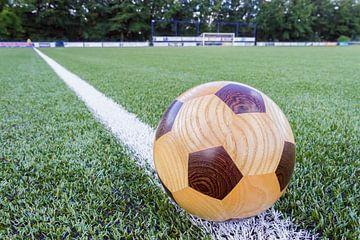 Holz Fußball liegt am Rande eines Fußballfeldes von Ben Schonewille