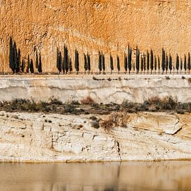 Rij van cypressen tegen een oranje rotsachtige achtergrond von Wout Kok