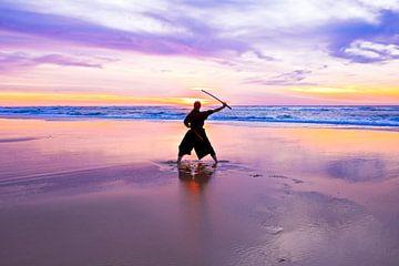 Junge Samurai-Frau mit japanischem Schwert (Katana) bei Sonnenuntergang am Strand von Nisangha Masselink