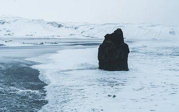 Rock in surf sur la plage de sable noir de Reynisfjara en Islande sur Michiel Dros