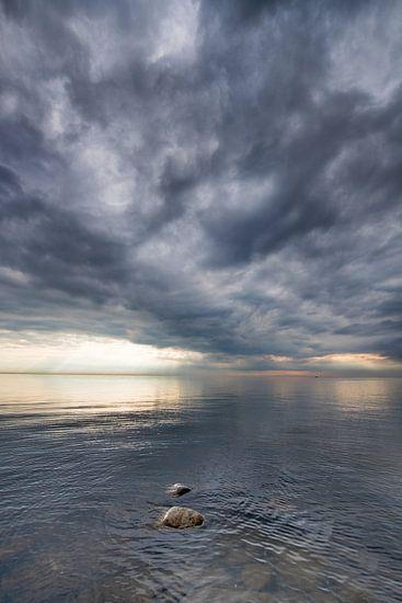 Wolkenlucht boven een spiegelend wateroppervlak vanhet IJsselmeer