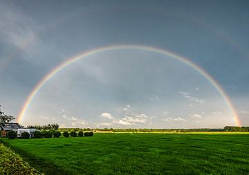 Regenboog boven een weiland sur Arnold de Gans