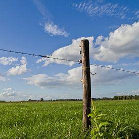 Weidepaal in een grasland met hollandse wolken van FHoo