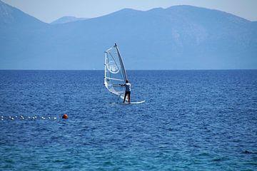 einsamer Windsurfer weiß in blauer Landschaft von wil spijker