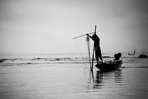 Silhouet van een visser met zijn visnet op het Indiemeer in Myanmar