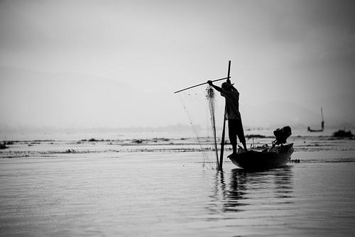 Silhouet van een visser met zijn visnet op het Indiemeer in Myanmar van