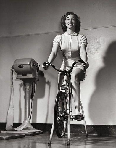 Historisch beeld jonge vrouw op fitnessapparaat in sportzaal