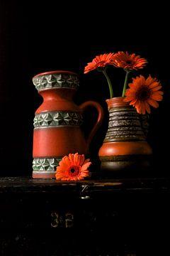 Abbildung von Vasen aus den 70er Jahren mit orangefarbenen Gerberas. von Therese Brals