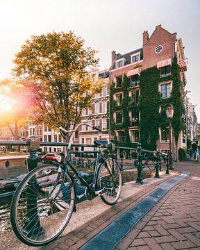 Fiets op een brug over de gracht in Amsterdam tijdens zonsondergang van Michiel Dros