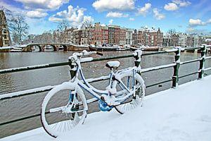 Besneeuwde fiets aan de Amstel in Amsterdam Nederland in de winter