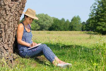 Vrouw schrijft bij boom in natuur van Ben Schonewille