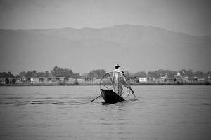 Visser in Myanmar op het Indiemeer met groot visnet op zijn houten boot.