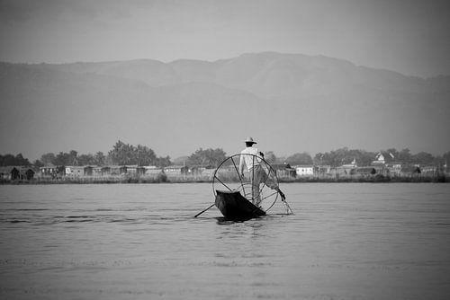 Visser in Myanmar op het Indiemeer met groot visnet op zijn houten boot.  von