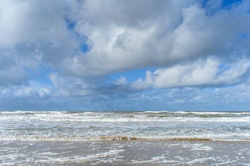 Witte wolken boven stormachtige zee tegen blauwe lucht