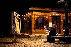 Un homme lit son journal sur un banc, le soir à Istanbul.