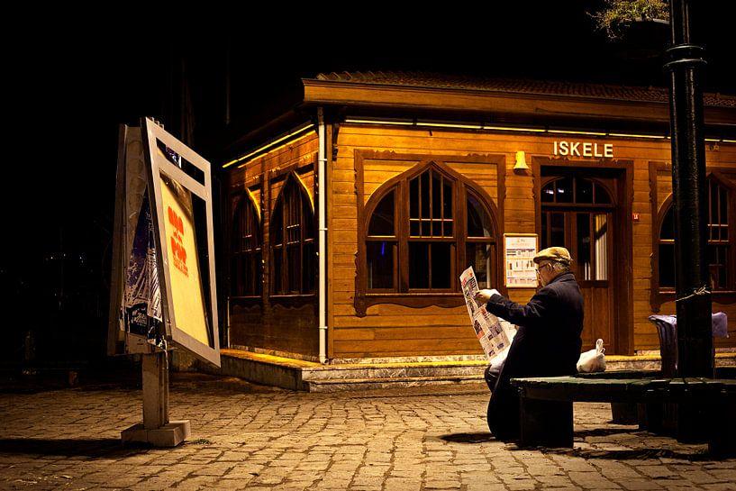 Un homme lit son journal sur un banc, le soir à Istanbul. sur Eyesmile Photography