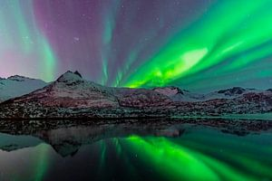 Aurore boréale ou Aurora Borealis sur un lac aux montagnes enneigées en hiver