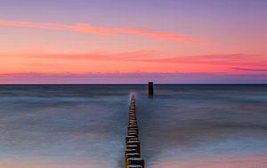 Kribben op zee in de zonsondergang