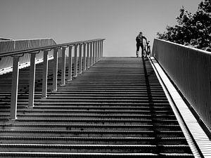 Met de fiets aan de hand over de brug. van