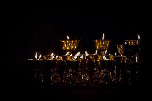 Brandende boterkaarsjes in een donkere tempel in Tibet