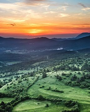 Wunderschöner Sonnenuntergang hinter grünen Feldern von Patrik Lovrin