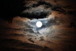 Maan verlicht kleurrijk de wolken van