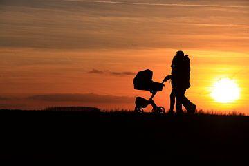 Koppel met kinderwagen zonsondergang van Bobsphotography