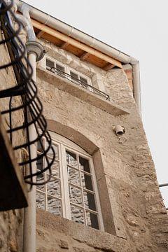 beige huis in Frankrijk met witte kozijnen en een zwart balkon. van Fotograaf Elise