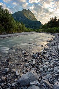 Une rivière le long des montagnes pendant le coucher du soleil. sur Robin van Maanen