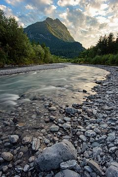 Een rivier langs de bergen tijdens zon ondergang.
