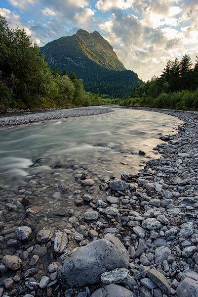Een rivier langs de bergen tijdens zon ondergang. van Robin van Maanen