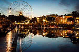 Stadsgezicht van Nice, Frankrijk, tijdens zonsondergang met reuzenrad en weerspiegeling van