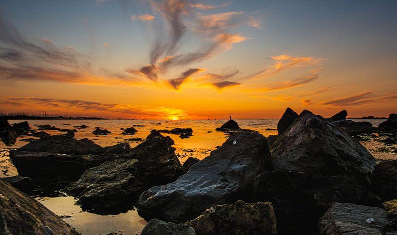 Zonsondergang tijdens eb op zee. van Brian Morgan