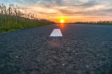 Zonsondergang boven asfalt weg van Fotografiecor .nl