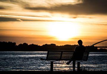 zitten bij zonsondergang van Rick Koppelaar
