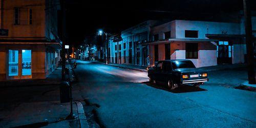 Een oude auto rijdt 's nachts door een donkere straat in Cuba