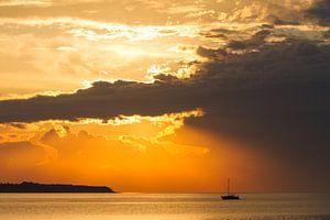 Zonsondergang op zee met zeilboot