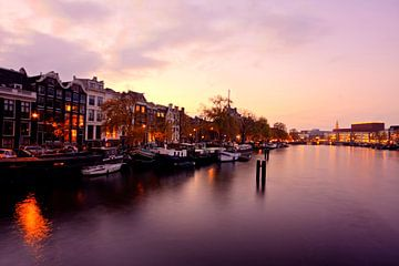 Stadsgezicht van Amsterdam aan de Amstel in Nederland bij avond van Nisangha Masselink