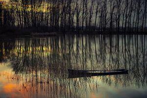Half gezonken bootje bij zonsondergang.