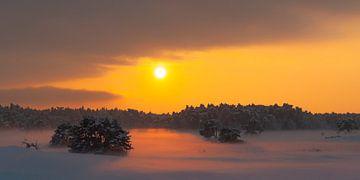 Bunter Wintersonnenuntergang über dem Schnee bedeckte Ebenen in der Natur von Sjoerd van der Wal