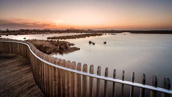 Zonsondergang bij hekwerk in het natuurgebied de Onlanden van Martijn van Dellen