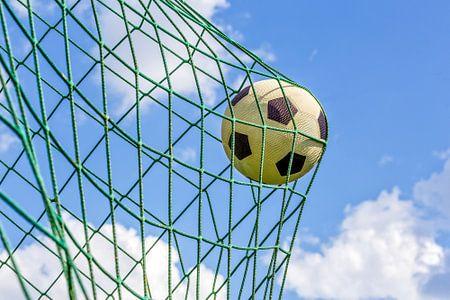 Voetbal in net van goal tegen blauwe lucht
