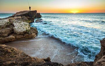 Rotskust met visser in de zonsondergang van videomundum