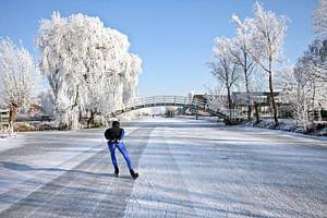 Eenzame schaatser op bevroren sloot op het platteland in Nederland
