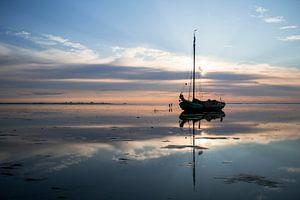 Drooggevallen zeilschip in uitgestrekt Waddenlandschap bij zonsondergang