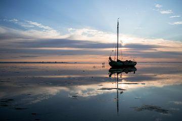 Drooggevallen zeilschip in uitgestrekt Waddenlandschap bij zonsondergang van Hette van den Brink