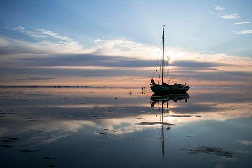 Drooggevallen zeilschip in uitgestrekt Waddenlandschap bij zonsondergang van