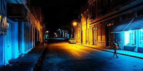 Wandelaar loopt in een donkere straat in Cuba verlicht door een lantaarn