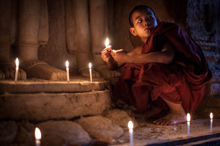 BAGHAN,MYANMAR, DECEMBER 12 2015 -Jonge  monnik steekt kaarsen aan bij beeld van Budha
